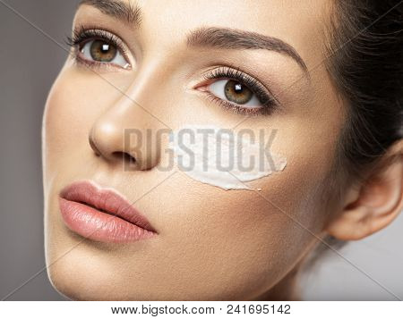 Beautiful face of young woman with cosmetic cream smear on face near eye.  Skin care  concept. Beauty treatment concept.