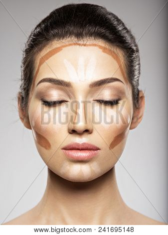 Cosmetic makeup tonal foundation is on woman's face.  Beauty treatment concept. Girl makes makeup.