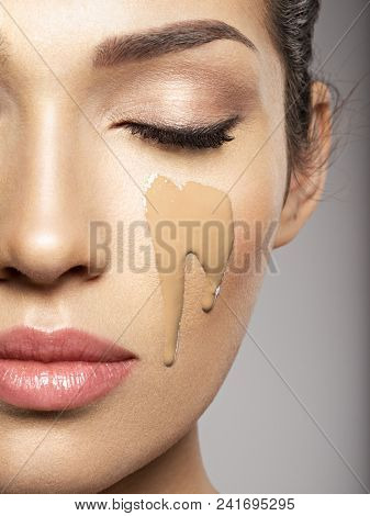 Liquid cosmetic makeup foundation is on the female face.  Beauty treatment concept. Girl makes makeup.