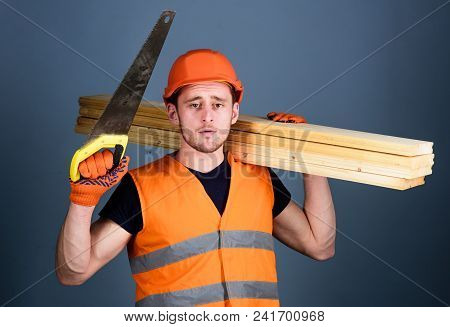 Man, Handyman In Helmet, Hard Hat Holds Handsaw And Wooden Beams, Grey Background. Woodcraft Concept