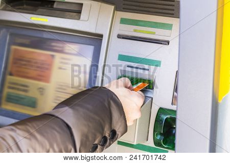Man Inserting Card In Atm. Close Up