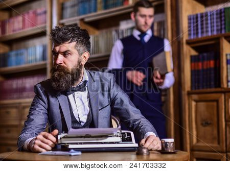 Man With Beard And Strict Face Work With Typewriter Near Man With Book On Background, Defocused. Men