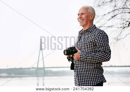 Photo Art. Positive Mature Man Holding Camera And Smiling