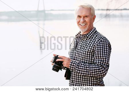 Wonderful Hobby. Merry Mature Man Carrying Camera And Smiling To Camera