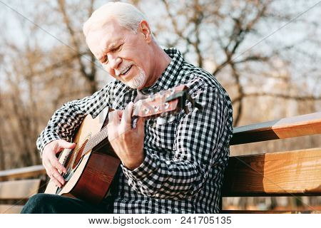 Soul Music. Low Angle Of Focused Mature Man Posing On Bench And Enjoying Guitar Play
