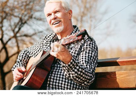 Connection Through Music. Low Angle Of Enthusiastic Mature Man Sitting In Park And Enjoying Guitar P