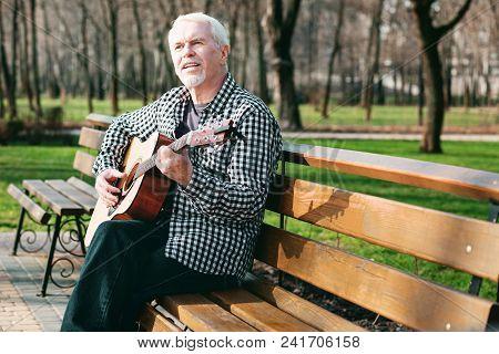 Guitar Cord. Pleasant Mature Man Singing And Playing Guitar