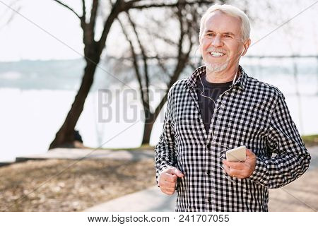 Great Mood. Energetic Senior Man Walking And Enjoying Music