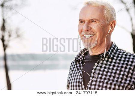 Favorite Song. Pleased Senior Man Posing On Blurred Background And Enjoying Music