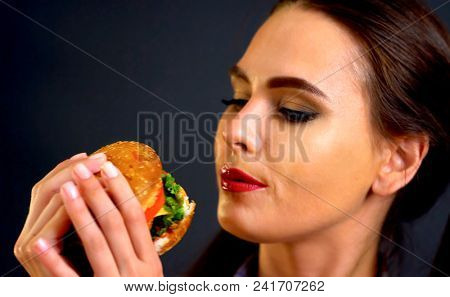 Woman eating hamburger. Girl wants to eat burger. Mom prepared dinner for her daughter. Portrait of person with good appetite have greedily dinner delicious sandwich on a black background.