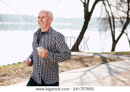 Morning Run. Merry Senior Man Running And Wearing Headphones