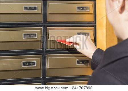 Woman Inserting Letter In A Mailbox. Detail