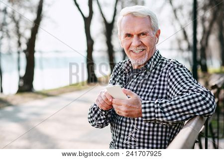 Music In Phone. Positive Senior Man Smiling To Camera And Listening To Music