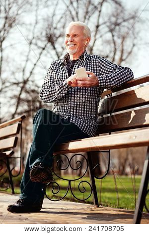 Music In Park. Low Angle Of Cheerful Senior Man Sitting On Bench And Listening To Music
