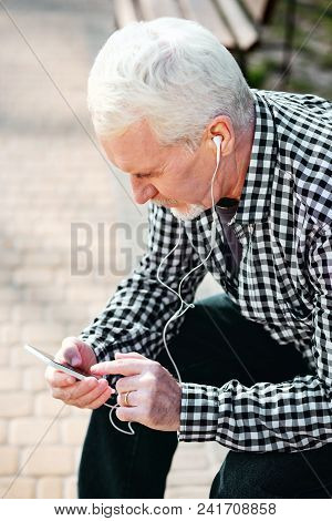 This Song. Top View Of Serious Senior Man Putting On Earphones And Listening To Music