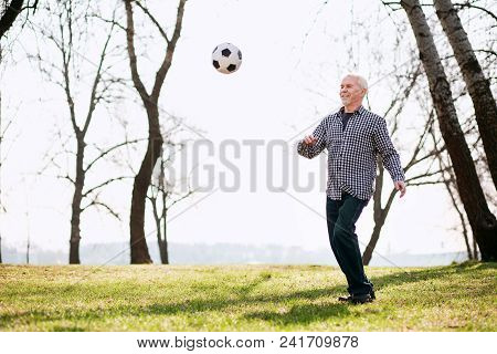Workout Outdoors. Vigorous Mature Man Exercising With Ball And Playing In Park