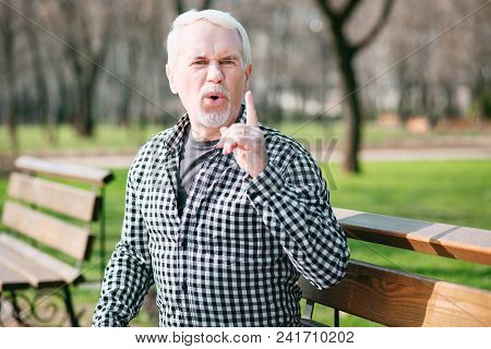 Stop This. Angry Senior Man Sitting On Bench And Rising Finger