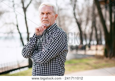 Where To Go. Thoughtful Senior Man Posing In Park And Touching Face