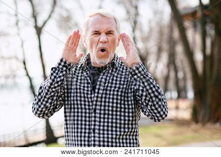 Come Here. Earnest Senior Man Standing In Park And Shouting