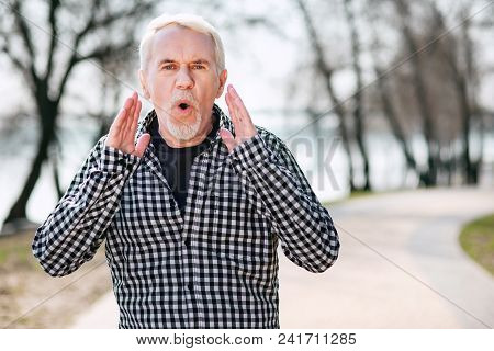 Stay There. Appealing Senior Man Staying In Park And Shouting