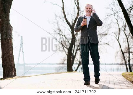 Phone Call. Low Angle Of Experienced Senior Businessman Going In Park And Talking On Phone