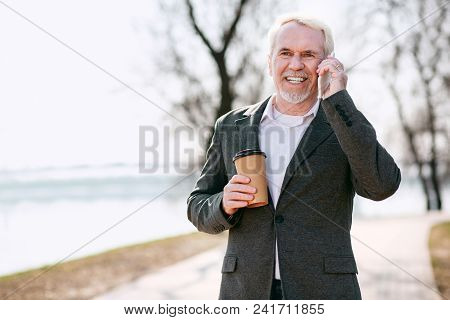 Drink And Talk. Happy Senior Businessman Posing In Park And Talking On Phone