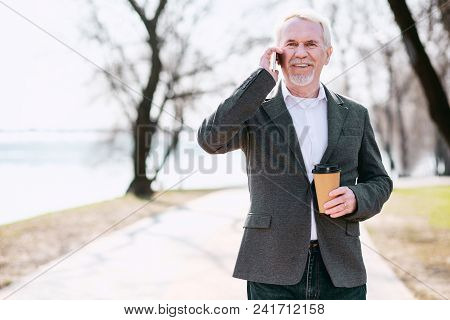 Business Deal. Optimistic Senior Businessman Enjoying Coffee In Park And Talking On Phone