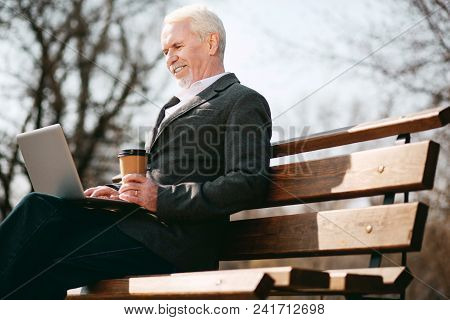 Outside Box. Low Angle Of Merry Mature Businessman Using Laptop While Holding Coffee