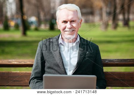 Favorite Work. Pleased Mature Businessman Using Laptop While Grinning To Camera
