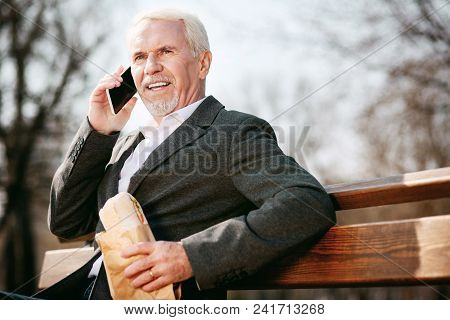 Fast And Tasty. Low Angle Of Satisfied Mature Businessman Talking On Phone And Biting Sandwich
