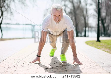 Ready Steady Go. Enthusiastic Mature Man Preparing Before Running In Park