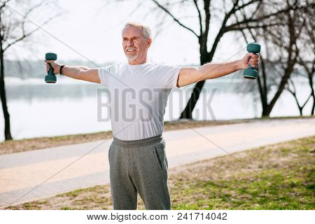 Sportive Spirit. Vigorous Mature Man Training With Dumbbells And Standing In Park