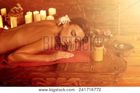 Massage of woman in spa salon. Girl on candles background in therapy room. Luxary interior in oriental therapy salon. Sun flare for female have relax after sport. Light from right.