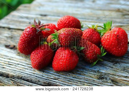 Fresh red berries. Strawberries on the wooden table. Strawberry background. Fresh juicy red berries in the garden on table. Summer vacation. Summer berries. Delicious and healthy vegetarian food