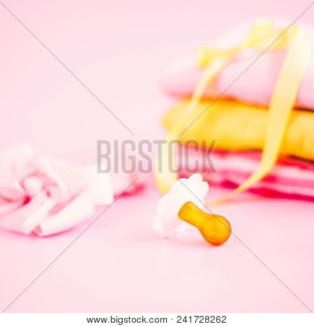 Newborn Stuff, Clothes And Pacifier For Baby Girl On Pink Background