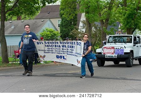 WEST SAINT PAUL, MN/USA - MAY 19, 2018: Members of local Democratic-Farmer-Labor Party organizing unit hold sign and march in West Saint Paul Days parade followed by supporters of local candidate.