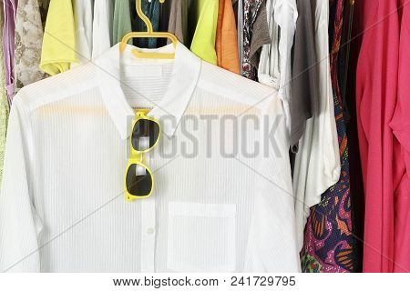 White Blouse With Sunglasses On Hanger In Front Of Other Female Clothes