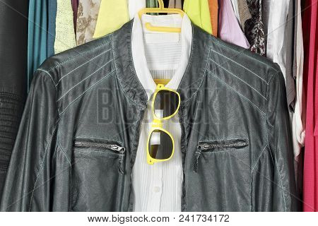 Green Leather Jacket And White Shirt With Sunglasses In The Closet