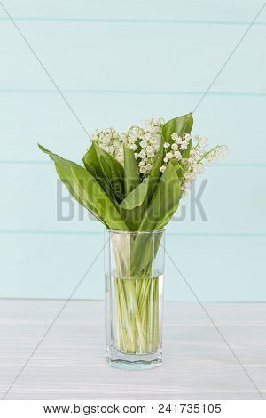 Lilies Of The Valley On A Turquoise Wooden Background. A Bouquet Of Lilies Of The Valley. Lilies Of