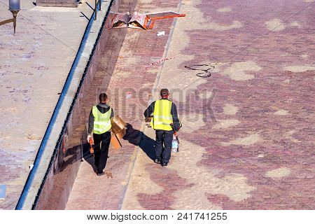 View Of Men In Uniform Making Paved Sidewalk In Pedestrian Area