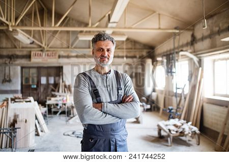 Portrait Of A Mature Man Worker In The Carpentry Workshop, Arms Crossed.