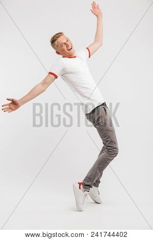 Full length portrait of cheerful teen man wearing casual clothing smiling and spreading arms isolated over white background