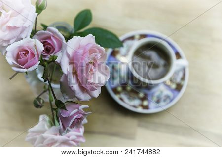 Background. Flowers. Roses. Flowers background image. Flowers and coffee cup background space for text. Roses flowers background wooden table. Pink roses and coffee cup background with space for text. Background. Flowers. Coffee cup. Flower. Pink roses an