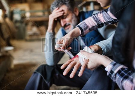 An Unrecognizable Woman Bandaging A Hand Of A Man Worker After An Accident In Carpentry Workshop. A