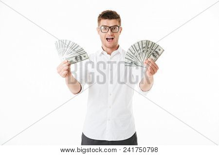 Portrait of an excited young man in eyeglasses holding money banknotes isolated over white background