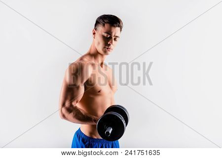 Half-turned View Portrait Of Handsome Sportive Muscular Trainer Pushing Up A Dumbbell And Looking On