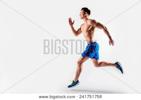 Ready, Steady, Go! Handsome Muscular Strong Determined Guy Dressed In Blue Shorts And Sneakers Is Ru