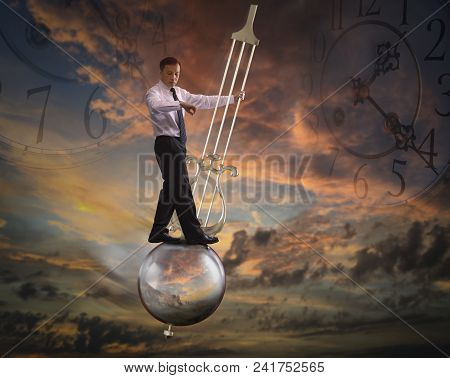 Businessman Standing On A Pendulum Of A Grandfather Clock Swinging In The Air On Twilight Background