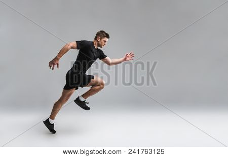Full length portrait of a focused young sportsman running fast isolated over gray background