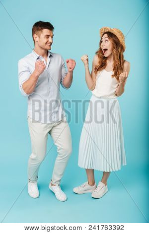 Image of young excited caucasian people man and woman isolated over blue background make winner gesture screaming.